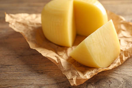 Parchment paper with cut wheel of delicious cheese on wooden table, closeup