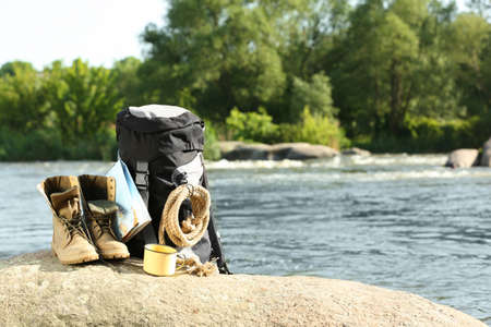 Backpack and camping equipment on rock near river. Space for text