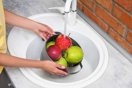 Woman washing fresh apples in kitchen sink, closeup