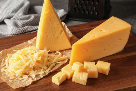 Grated and cut delicious cheese on board