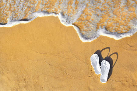 White flip flops on sand near sea, top view with space for text. Beach accessories Stockfoto