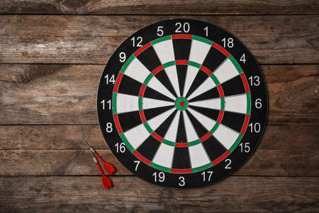 Dart board with color arrows on wooden background, top view. Space for text Banco de Imagens - 128781424