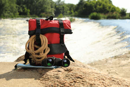 Backpack and camping equipment on stone near river. Space for text