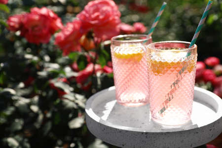 Glasses of pink lemonade on white table in rose garden. Space for text