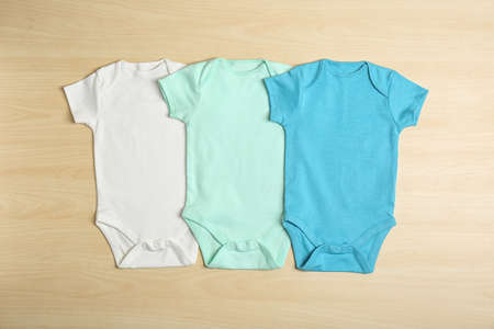Different baby bodysuits on wooden background, top view
