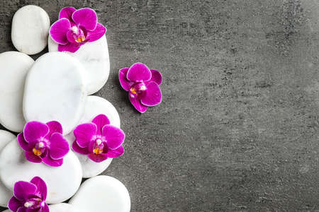 White spa stones and orchid flowers on grey background, flat lay. Space for text