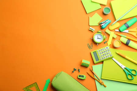 Different bright school stationery on orange background, flat lay. Space for text