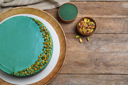 Flat lay composition with spirulina cheesecake on wooden table. Space for text