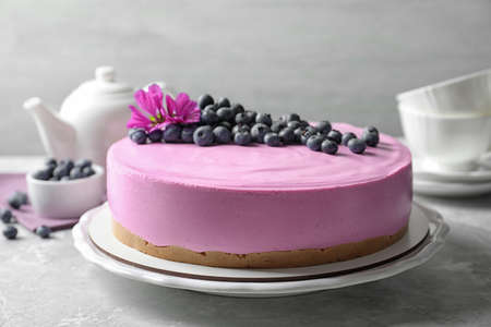Plate with tasty blueberry cake on light grey table