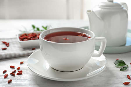 Healthy goji tea in cup on white wooden table