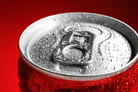 Wet closed can on red background, closeup