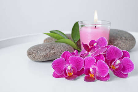 Spa stones, orchid flowers and candle on white table Banco de Imagens