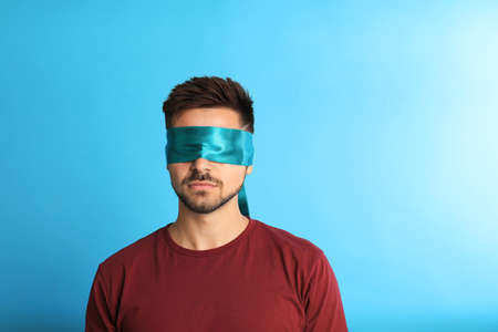 Young man with blindfold on blue background, space for text Standard-Bild