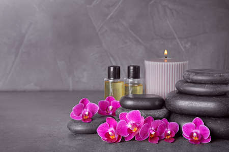 Composition with spa stones and orchid flowers on grey background. Space for text Banco de Imagens