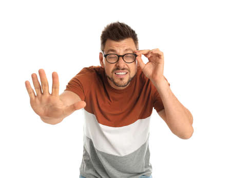 Man with vision problems wearing glasses on white background