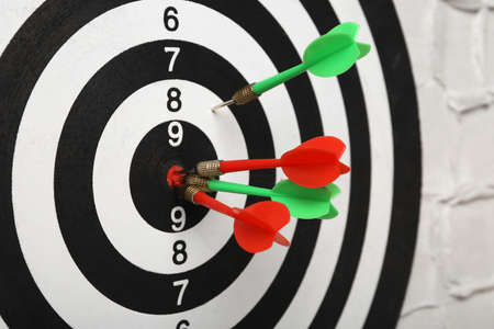 Arrows hitting dart board on white textured wall, closeup Banco de Imagens - 128788785