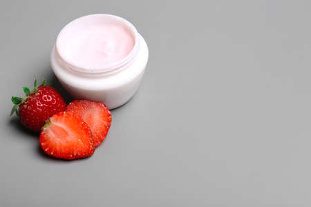 Jar of body cream and strawberries on grey background. Space for text Banco de Imagens