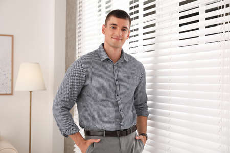 Portrait of handsome young man near window blinds indoors