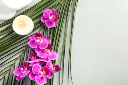 Flat lay composition with orchid flowers and spa stones on grey surface. Space for text
