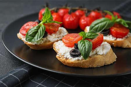 Plate of delicious tomato bruschettas on table, closeup Stockfoto - 128789138
