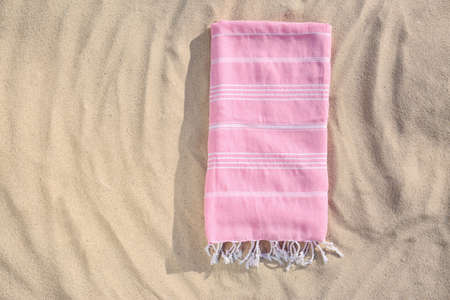 Folded new towel on sand, top view with space for text. Beach object