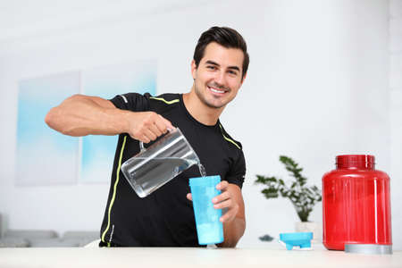 Young athletic man preparing protein shake at home