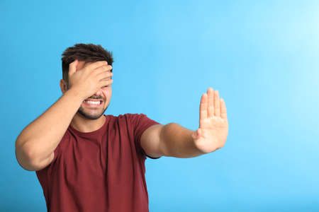 Young man being blinded on blue background