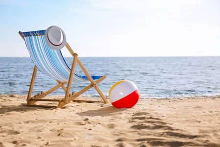Lounger, hat and inflatable ball on sand near sea, space for text. Beach objects
