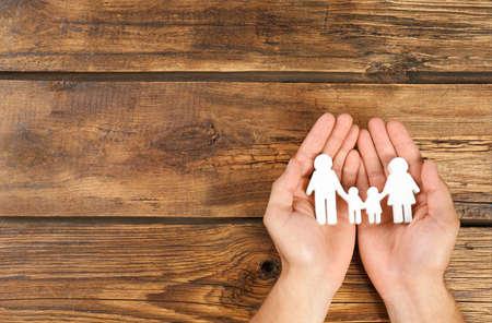 Giovane che tiene la figura della famiglia nelle sue mani su sfondo di legno, vista dall'alto. Spazio per il testo Archivio Fotografico