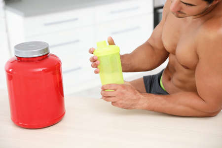 Young shirtless athletic man preparing protein shake at wooden table indoors, closeup view