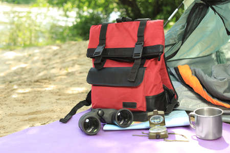 Camping equipment and modern tent in wilderness. Space for text