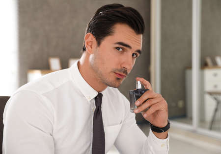 Handsome young man using luxury perfume indoors