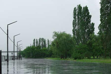 Empty city embankment under heavy rain on spring day