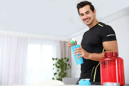 Young athletic man preparing protein shake at home, space for text Фото со стока