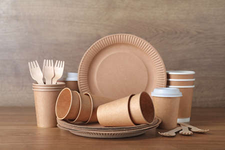 New paper dishware on wooden table. Eco life
