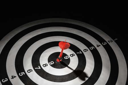 Red arrow hitting target on dart board against black background Banco de Imagens - 128788078