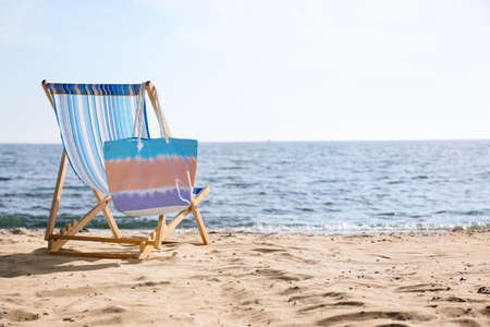 Lounger and bag on sand near sea, space for text. Beach objects Reklamní fotografie