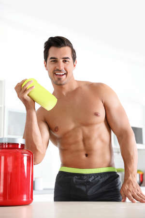 Young shirtless athletic man with protein shake powder in kitchen Фото со стока