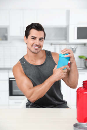 Young athletic man with protein shake powder in kitchen Фото со стока