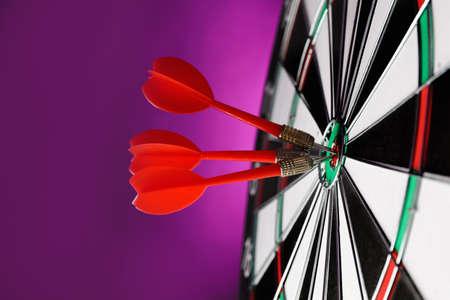 Red arrows hitting target on dart board against purple background Banco de Imagens - 128787989