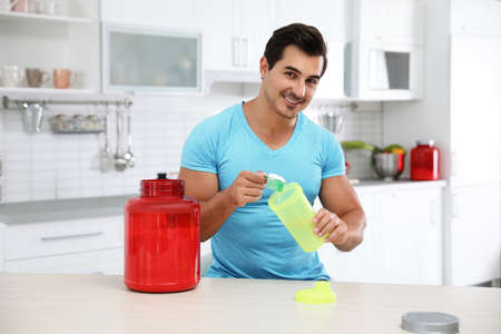 Young athletic man preparing protein shake in kitchen
