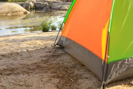 Modern camping tent on riverbank. Space for text Stockfoto