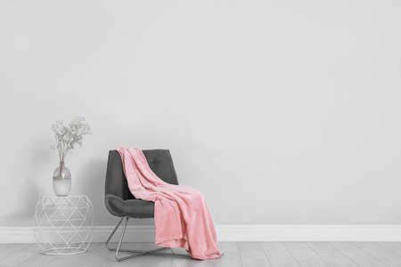 Stylish room interior with comfortable chair and plaid near white wall. Space for text Stock fotó
