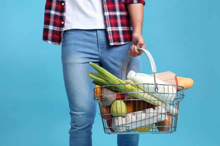Man with shopping basket full of products on blue background, closeup Фото со стока - 128781795