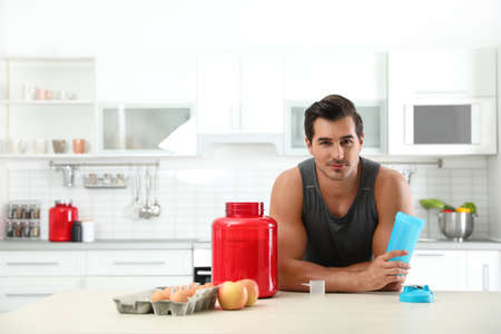 Young athletic man with ingredients for protein shake in kitchen, space for text Фото со стока