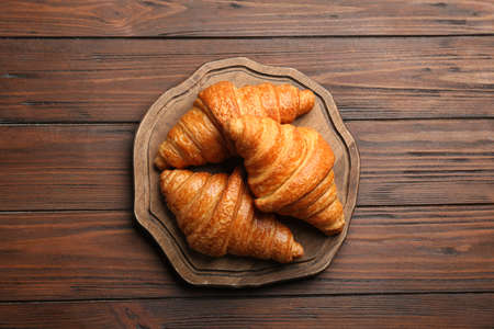 Board with tasty croissants on wooden background, top view. French pastry