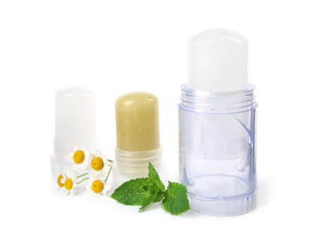 Natural crystal alum stick deodorants with chamomiles and mint on white background