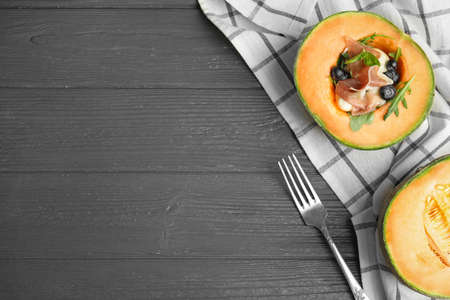 Flat lay composition of melon with prosciutto on grey wooden table. Space for text
