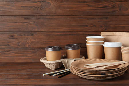 New paper dishware on dark wooden table, space for text. Eco life