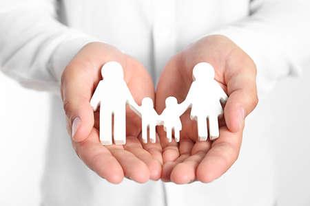 Jonge man met houten familie figuur op witte achtergrond, close-up van handen Stockfoto